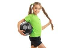 绿色衬衣的小逗人喜爱的女孩有足球的在手上 免版税图库摄影