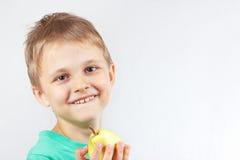 绿色衬衣的小滑稽的男孩用黄色水多的梨 免版税图库摄影