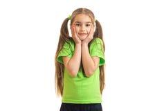 绿色衬衣的逗人喜爱的小女孩看并且微笑照相机 免版税图库摄影
