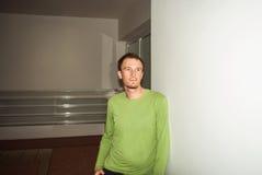 绿色衬衣的年轻人,站立在墙壁和今后看 图库摄影