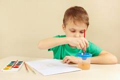 绿色衬衣绘画的年轻男孩与水彩 免版税库存照片