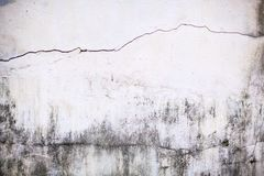 色被绘的简单老年迈的白色退了色在破裂的水泥具体房子墙壁表面背景的被风化的织地不很细样式 库存照片