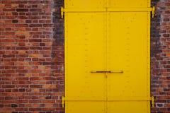 黄色被绘的金属门和砖墙 库存图片