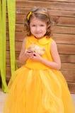 黄色褂子的卷曲女孩有鸡的 库存照片