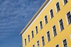 黄色议院和多云天空 免版税库存照片