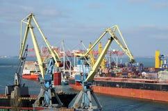 黄色起重机和集装箱船在傲德萨海港,乌克兰 免版税库存图片