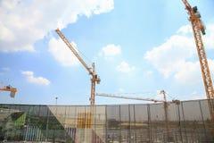黄色起重机在有蓝天和云彩的建造场所,当建筑学背景 免版税库存图片
