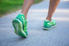 绿色跑鞋的跑步的妇女 免版税库存图片