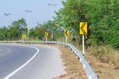 黄色路标警告前面危险曲线的司机 图库摄影