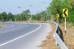黄色路标警告前面危险曲线的司机 免版税图库摄影