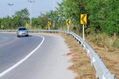 黄色路标警告前面危险曲线的司机 免版税库存图片