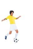 黄色踢的球的足球运动员 免版税库存图片
