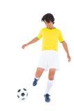 黄色踢的球的足球运动员 库存图片
