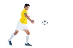 黄色踢的球的足球运动员 免版税图库摄影