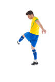 黄色踢的足球运动员 免版税库存图片