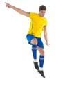 黄色踢的足球运动员 免版税图库摄影