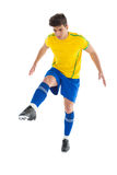 黄色踢的足球运动员 库存图片