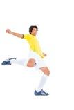 黄色踢的足球运动员 免版税库存照片