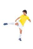 黄色踢的足球运动员 库存照片