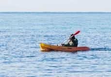 绿色连衫裤的渔夫在海的橙色皮船漂浮 免版税图库摄影