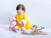 黄色连裤外衣的女婴选择围嘴 库存照片