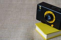 黄色迷你笔记薄和一台小电影减速火箭的照相机 免版税库存图片