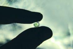 绿色透镜在手中在云彩背景 库存图片