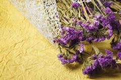 紫色逗人喜爱的花束的顶视图烘干了在明亮的黄色背景的花 与紫罗兰色花的黄色织品 免版税库存照片