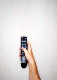 黑色遥控从电视在一只男性手上在浅灰色的背景 库存照片