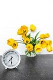 黄色郁金香和一个减速火箭的时钟花束  免版税库存图片