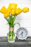 黄色郁金香和一个减速火箭的时钟花束  图库摄影