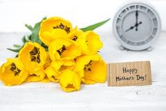 黄色郁金香和一个减速火箭的时钟花束  库存图片