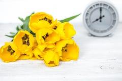黄色郁金香和一个减速火箭的时钟花束  免版税库存照片