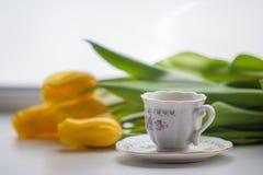 黄色郁金香和一个杯子热的茶或咖啡 库存照片