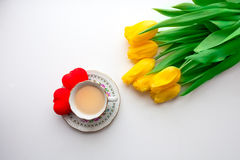 黄色郁金香和一个杯子热的茶或咖啡 免版税图库摄影