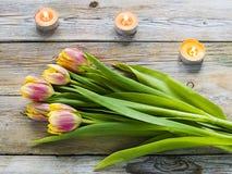 紫色郁金香和蜡烛在老木桌上 免版税库存照片