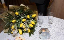 黄色郁金香和玻璃花束在一张桌上在餐馆 库存图片