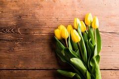 黄色郁金香花束反对棕色木背景的 免版税库存照片