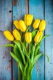 黄色郁金香花束在蓝色土气背景的 免版税库存图片