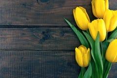 黄色郁金香花束在黑暗的土气木背景的 库存图片