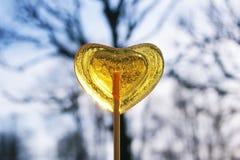 黄色金黄心形的lollipo 库存图片