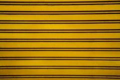 黄色钢路辗快门门背景(与h的车库门 免版税图库摄影