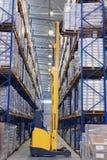 黄色铲车提高上货盘在机架的架子顶部 免版税库存图片