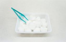 绿色镊子和棉花塑胶容器 免版税库存图片