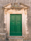 绿色门 木纹理 老破旧,被照耀的油漆 免版税库存图片