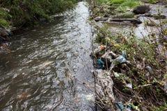 绿色附注污染水 在都市小河附近的垃圾 免版税库存图片