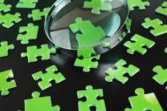 绿色难题和放大镜 免版税库存照片
