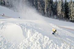 黄色雪制造商机器雪枪,在滑雪的雪大炮倾斜手段-做的雪标准设备设备创造bette 库存图片