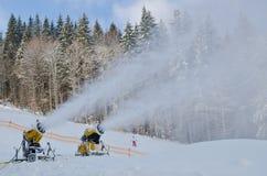 黄色雪制造商机器雪枪,在滑雪的雪大炮倾斜手段-做的雪标准设备设备创造bette 免版税库存图片