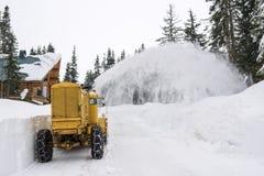 黄色雪犁清洁山路 免版税图库摄影